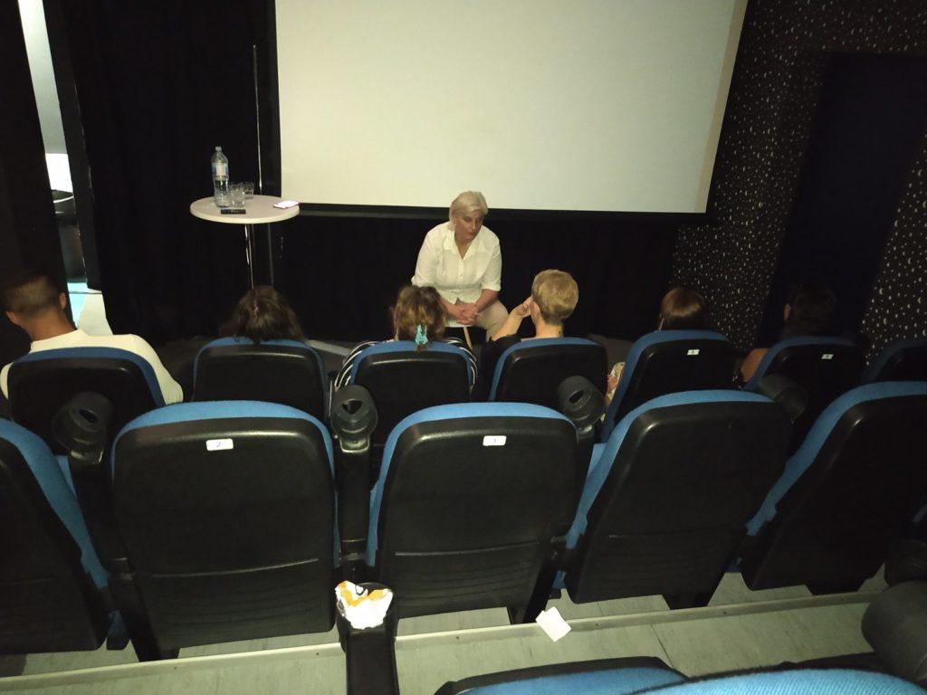 Žena u belom drži predavanje ispred nje su gledaoci koji sede u stolicama