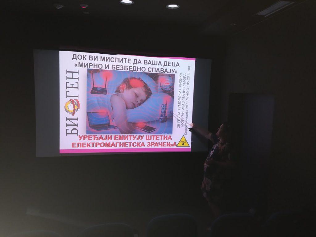 žena drži predavanje , nasslici projektora je dete koje spava a okolo su nacrtani svi aparati koji zrače  i utiču na zdravlje