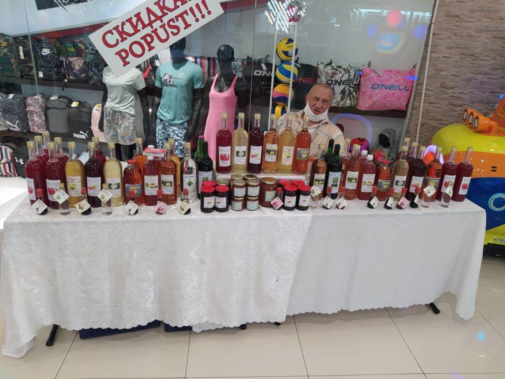 stariji čovek u svetloj košulju sedi za štandom na kojem su izloženi sokovi u flašama i džemovi u teglama