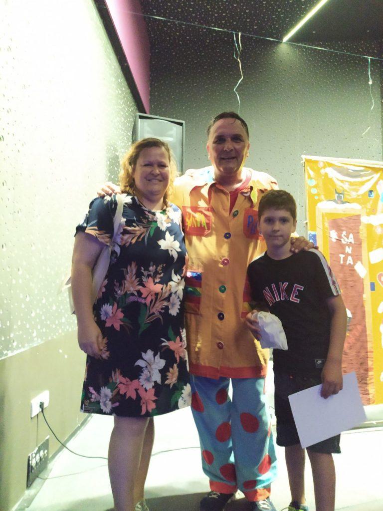 čovek u šarenom odelu gospođa u šarenoj haljini i dete sa crnom majicom stoje na pozornici