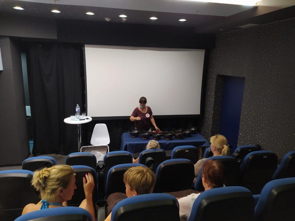 žena u ljubičastoj majici izbvodi meditaciju sa zvučnim činijama pred publikom koja sedi u gledalištu