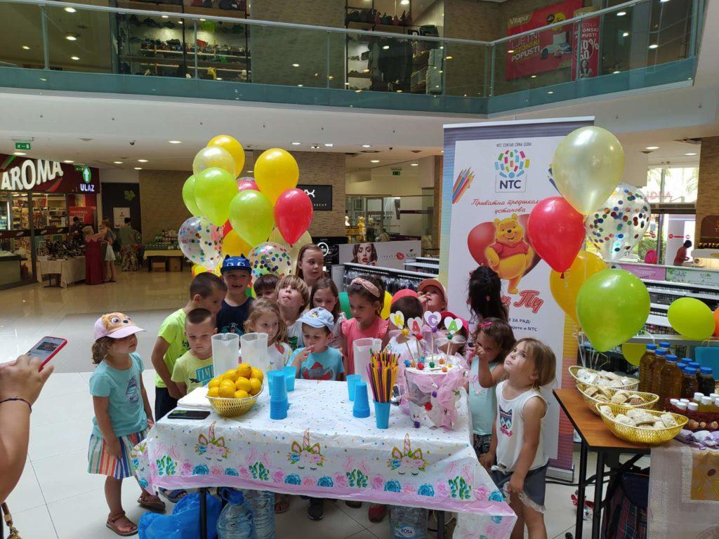 razigrana deca oko humanitarnog štanda sa limunadom u tržnom centru